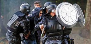 Riot police detain a demonstrator near the Maracana Stadium in Rio de Janeiro